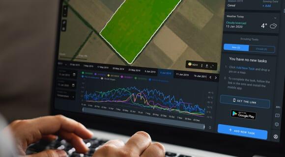 poljoprivrednik s prijenosnim računalom pomoću aplikacije Crop Monitoring